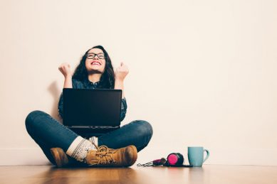 37880791 - girl sitting on the floor with a laptop raising his arms with a look of success